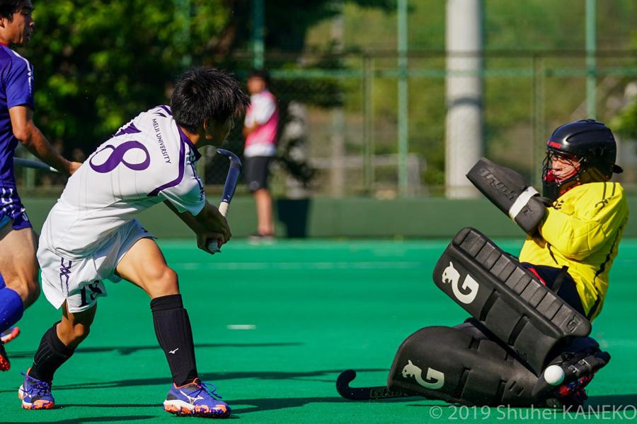 明治18番大森行洋選手(1年生)がシュートを狙うが、山梨学院1番山内大輝選手(1年生)が許さない。写真/金子周平