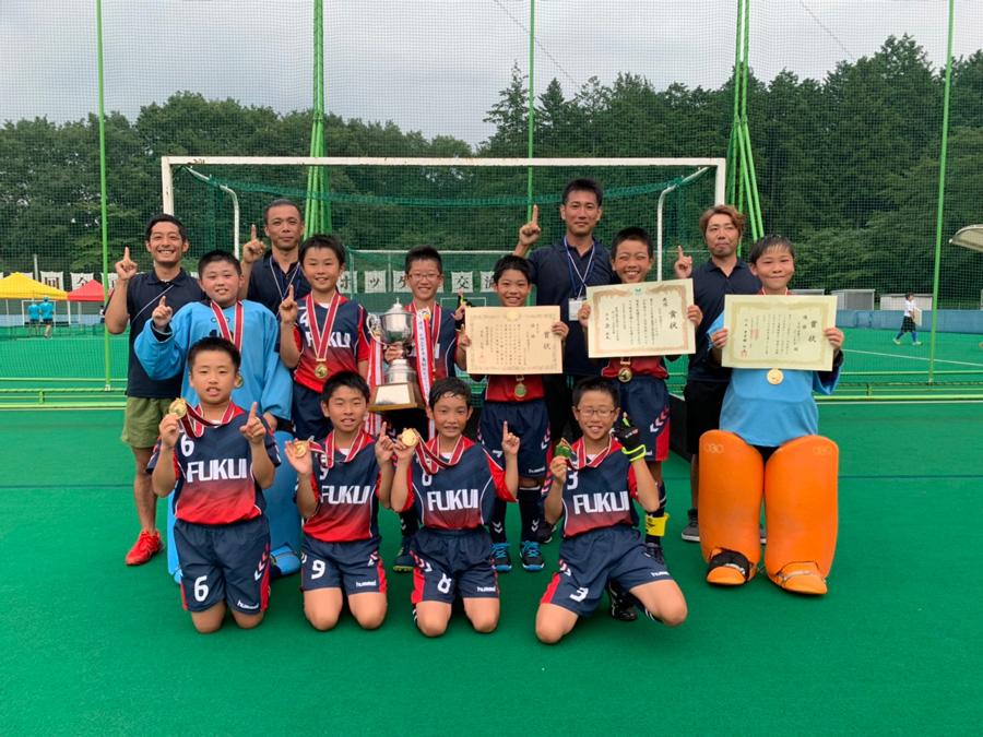 全国の舞台で練習の成果とチームワークを見せた糸生・常磐スポーツ少年団。優勝トロフィーや賞状を手に満面の笑顔。